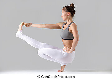 Woman doing Extended Hand to Big Toe pose with squat - Young...
