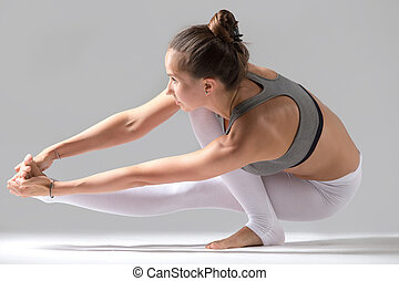 Woman doing Eka Pada Padangusthasana pose with squat - Young...