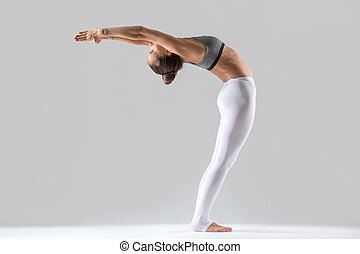Young woman in Ardha Chakrasana pose, grey studio background...