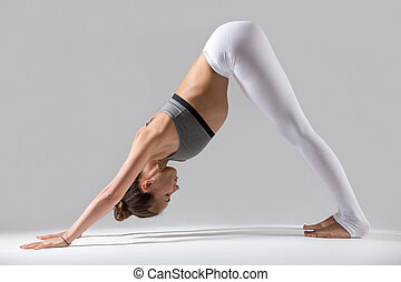 Young woman in Downward facing dog pose, grey studio...