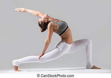Young woman in anjaneyasana pose, grey studio background -...
