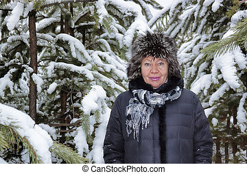 Portrait of smiling senior woman in a snow-covered winter...