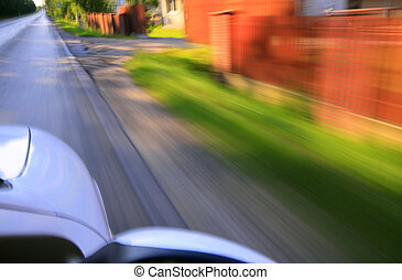 Road and car with motion blur effect. On right side hedge...