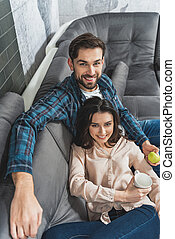 Cute man and woman relaxing in living room - Top view of...