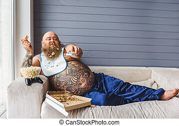 Relaxed thick guy entertaining with pizza and television -...