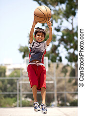 Young basketball player jumping high in air as he throws the...