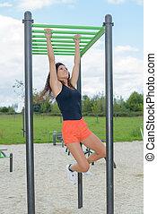 Woman climbing along monkey bars
