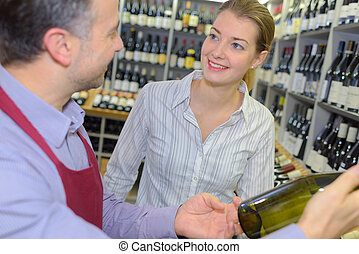 Wine merchant suggesting bottle to customer