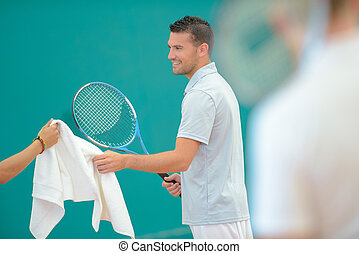 Tennis player being passed a towel