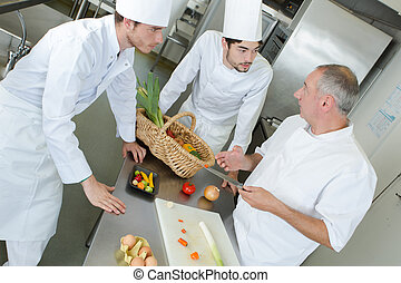 Chef teaching trainees about vegetables