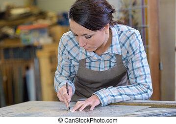 artisan worker drawing round stencil in workshop