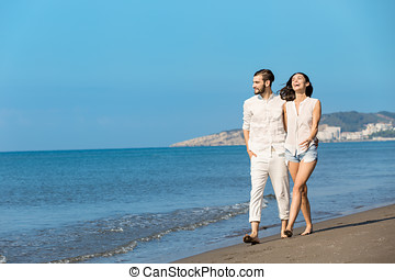 Couple walking on beach. Young happy interracial couple walking on beach smiling holding around each other.