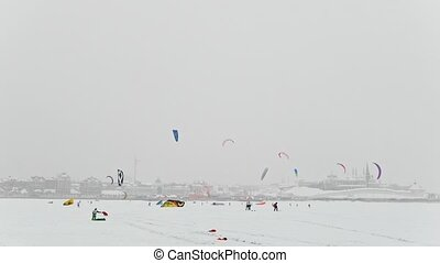 Winter extremal sport - many of snow-kite sportsmen's rides on the ice river in front of city at blizzard cloudy day