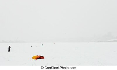 Snow-kite sportsmen on the ice river - winter extremal sport...