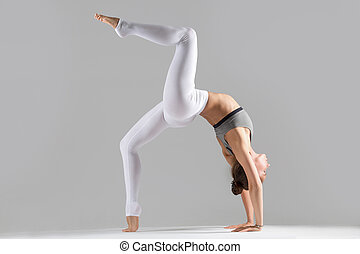 Young woman in One legged Wheel pose, grey studio - Young...