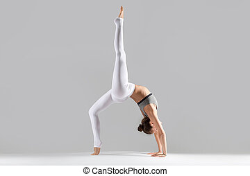 Young woman in One legged Wheel pose, grey studio background...