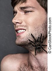 Portrait of a Young Handsome Man with Spider on His Face -...