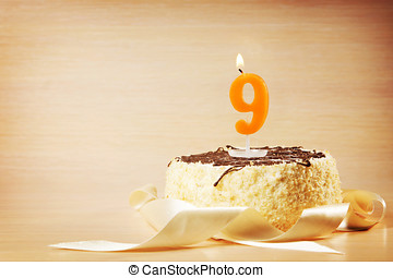 Birthday cake with burning candle as a number nine. Focus on...