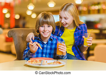 smiling boy and girl eating pizza or drinking juice indoor.