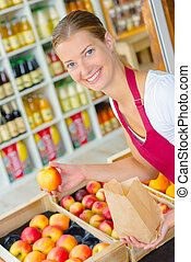 Supermarket worker in the fruit section