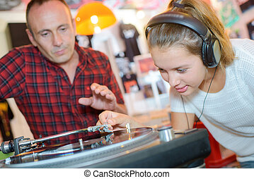 Young lady putting stylus onto record, man urging caution
