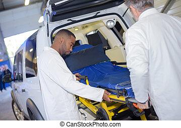Paramedics loading stretcher into emergency vehicle