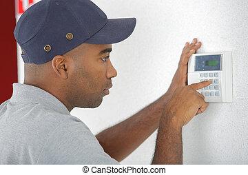 Man using alarm keypad