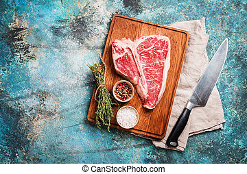 Raw T-bone Steak for grill or BBQ on cutting board over blue...