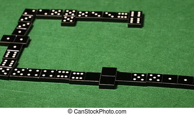 Configuration of played black domino tiles on green table -...
