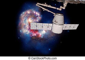 SpaceX Dragon over spiral galaxy. Elements of this image...