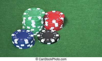 Set of casino chips on green table - Piles of green, red,...