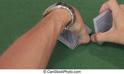 Male hands shuffle deck of poker cards