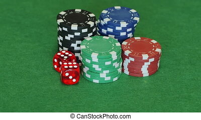 Poker chips and two red dice on table - Four sets of blue,...