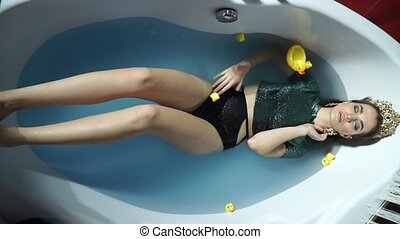 Fashion model lying in the bath and corrects earring -...