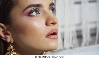 Close-up profile of a fashion model with bright makeup