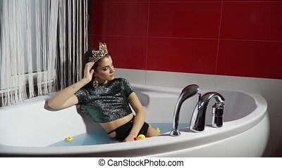 Proud and calm fashion model in a jacuzzi with water and a...