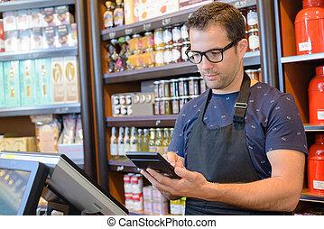 Shop keeper using calculator