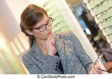 Lady in opticians looking at glasses