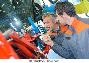 Two mechanics conferring