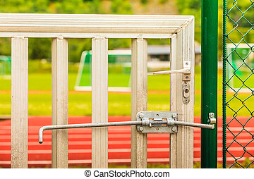 Padlock locked on stadium gate close up
