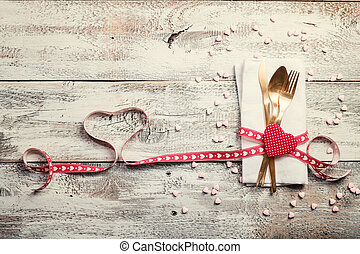 Valentines day table setting with napkin, knife, fork, red...