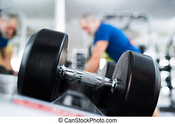 Close up of dumpbell, senior couple in gym working out with...
