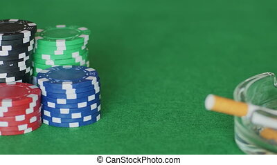 Chips, cards, ashtray on poker table - Sets of casino tokens...