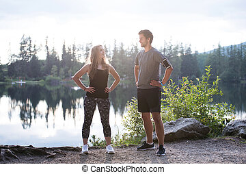 Beautiful young runners at the lake in green nature,...