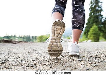 Legs of unrecognizable running woman in sports shoes
