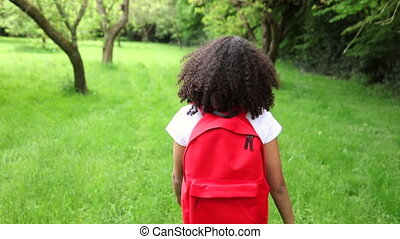 Beautiful happy mixed race African American girl teenager female young woman hiking with red backpack in green apple orchard