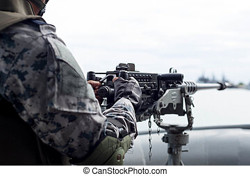 Selected focus Navy soldier hand on machine gun on navy ship