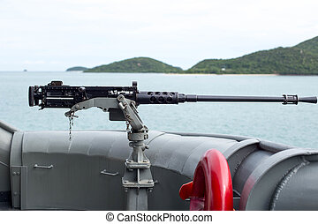 Machine gun on the side of Thai Navy warship with island and...