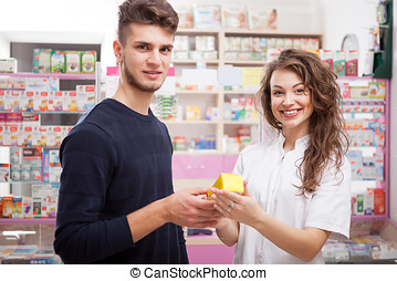 Smiling pharmacist and client looking at the camera