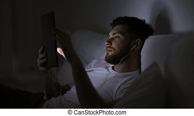 man with tablet pc and earphones in bed at night -...